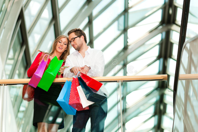 Man and woman in shopping mall with bags stock photo