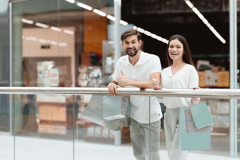 Man and woman in shopping mall. Couple is giving thumbs up on camera. royalty free stock photo
