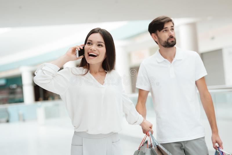 Man and woman in shopping mall. Woman wants to go to store but man is tired. Man and women with shopping bags in shopping mall. Woman wants to go to store but stock images