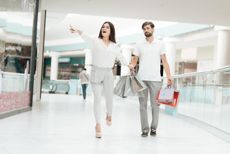 Man and woman in shopping mall. Woman wants to go to store but man is tired. Man and women with shopping bags in shopping mall. Woman wants to go to store but stock image