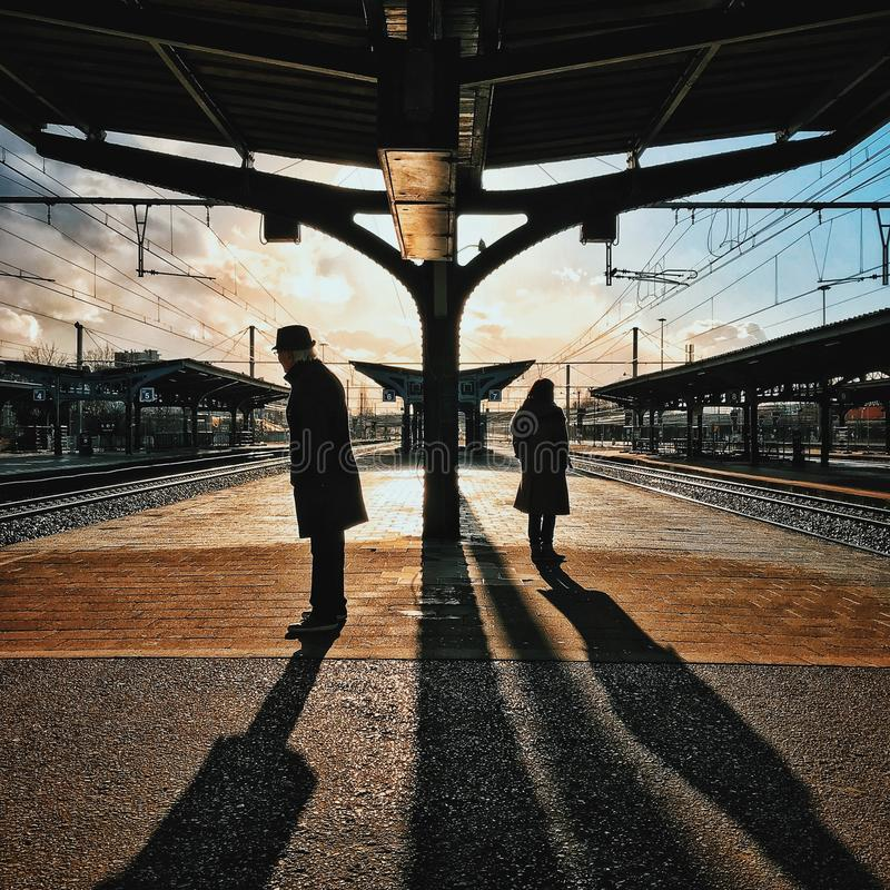 Man and Woman Silhouette Standing on Brown Ground at Daytime stock photography