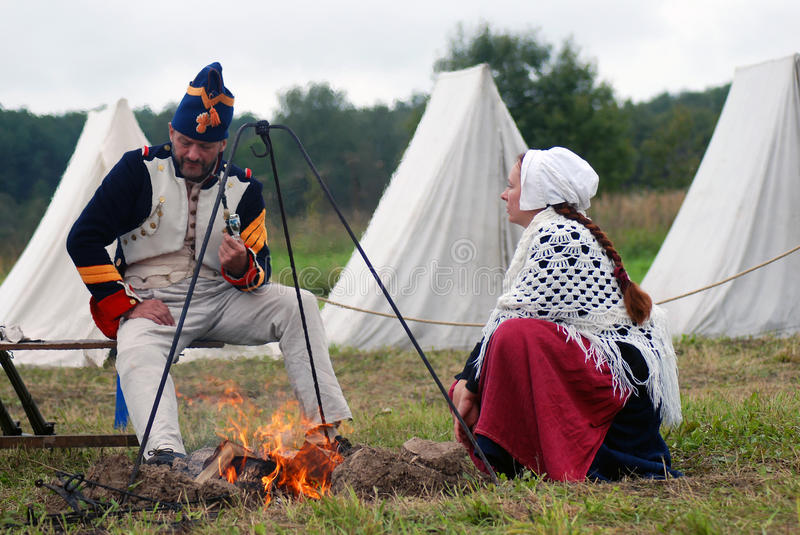 Man and woman sit by fire at Borodino battle historical reenactment in Russia. BORODINO, MOSCOW REGION - SEPTEMBER 04, 2016: Man and woman sit by fire at royalty free stock images