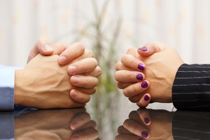 Man and woman sits at a desk with hands clasped. marital problem royalty free stock photography