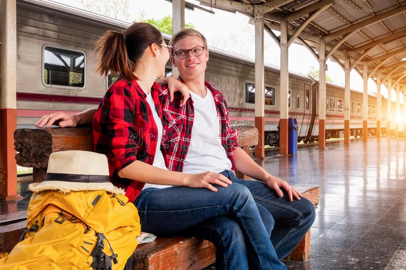 Man and Woman Sitting on Brown Wooden Bench at the Train Station royalty free stock image