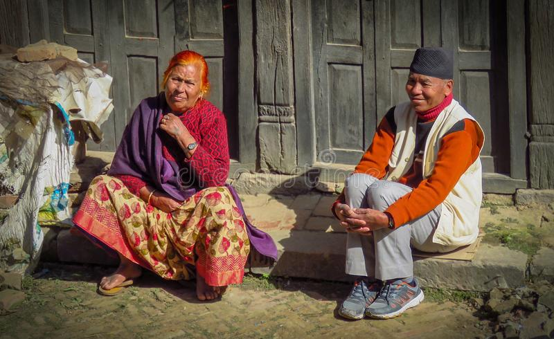 Man and woman sitting on the curb watching people go by, Bhaktapur, Nepal. Bhaktapur, Nepal - 11/21/2017: man and woman sitting on the curb at the side of the royalty free stock images