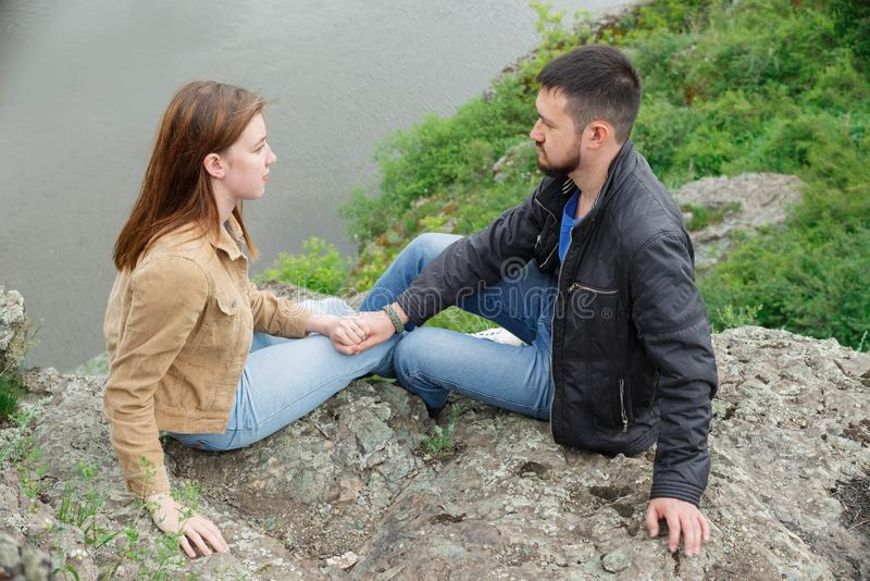 A man and a woman are sitting face to face on a stone platform stock photography