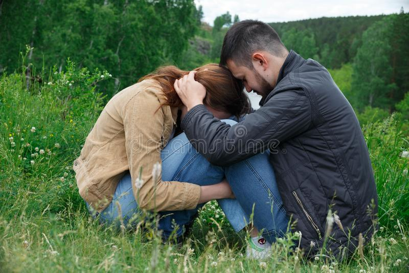 A man and a woman are sitting on a hill facing each other royalty free stock photo