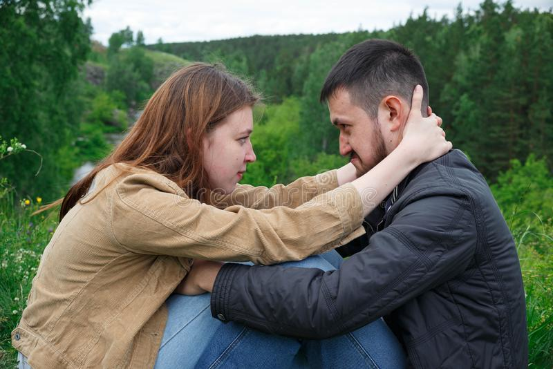 A man and a woman are sitting on a hill facing each other royalty free stock image