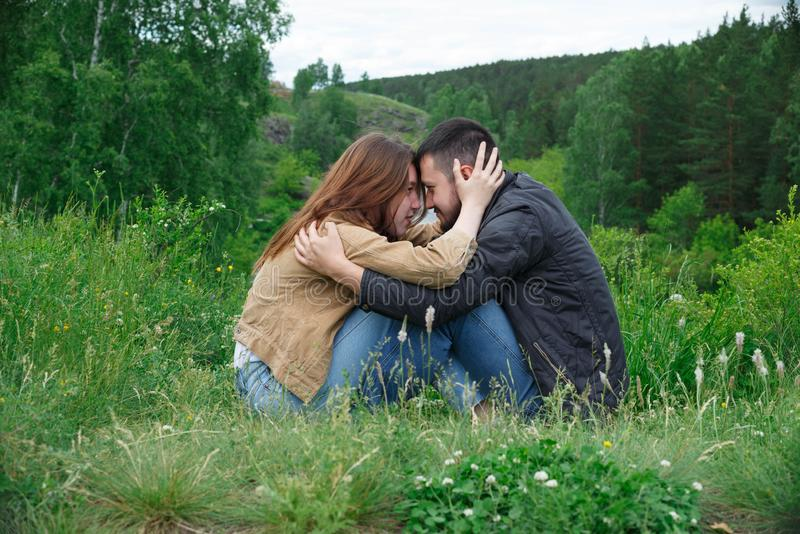 A man and a woman are sitting on a hill facing each other royalty free stock photography