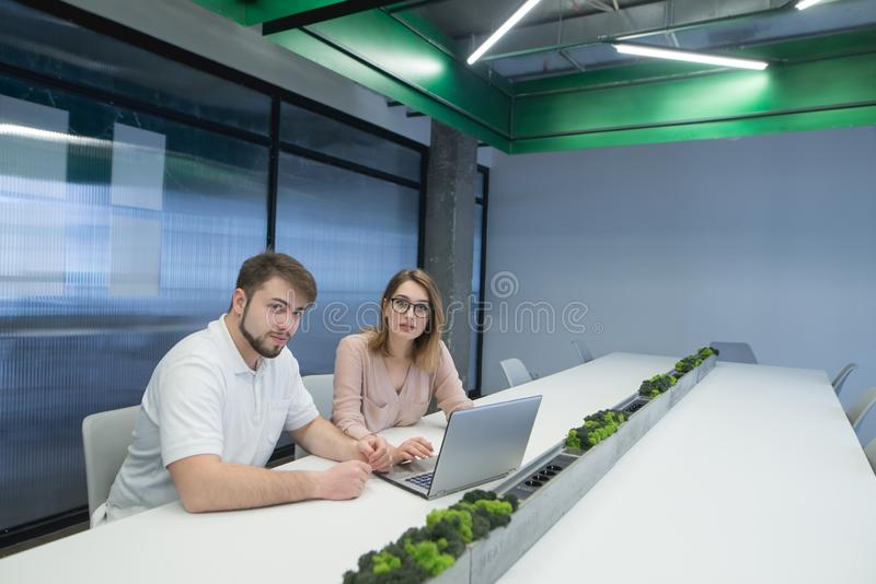 Man and a woman are sitting at the office near the desk at nobeboard and looking at the camera stock photos