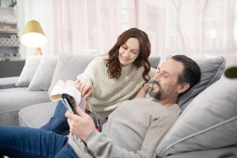 Man and woman sitting on the sofa choosing fabric stock image