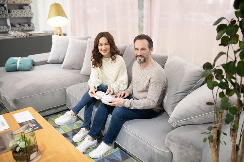 Man and woman sitting on the sofa in a furniture salon royalty free stock photography