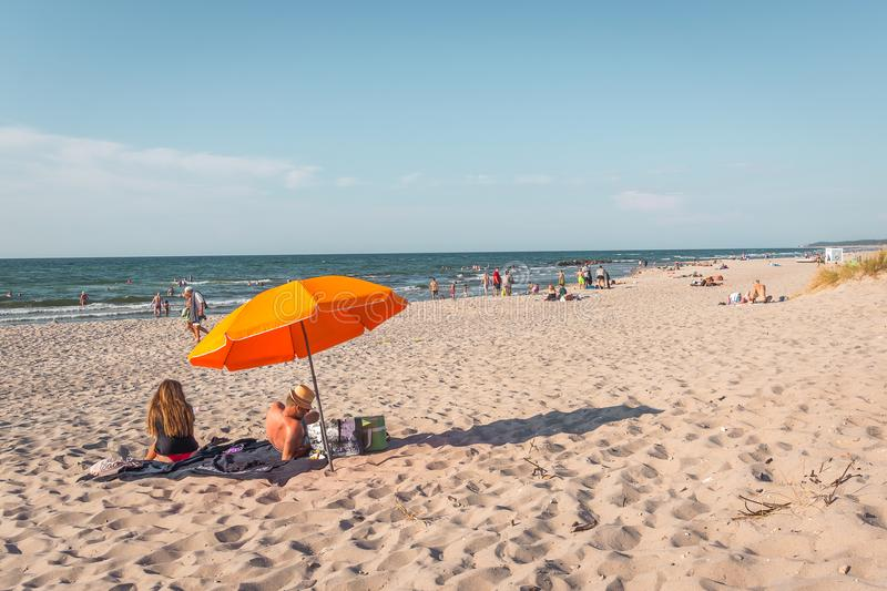 Man and woman sitting under an umbrella on the beach. Man and woman sitting on a blanket under an orange umbrella on the beach in the afternoon sunshine, Rorvig royalty free stock photos