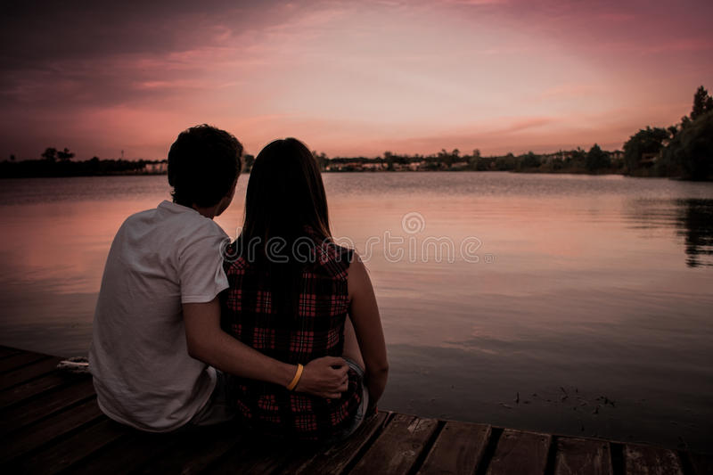 Man And Woman Sitting At Wooden Surface With Man's Hand On Woman's Waist Looking At Sunset Beside A Lake Free Public Domain Cc0 Image