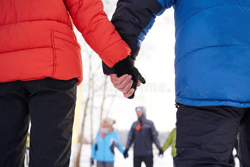 Man and woman in ski suits hold hands in cold winter royalty free stock photos