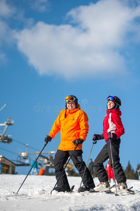 Man and woman skiers with skis at winter resort. Couple holding skis smiling on mountain top together at a winter resort with ski lifts and blue sky in royalty free stock photography