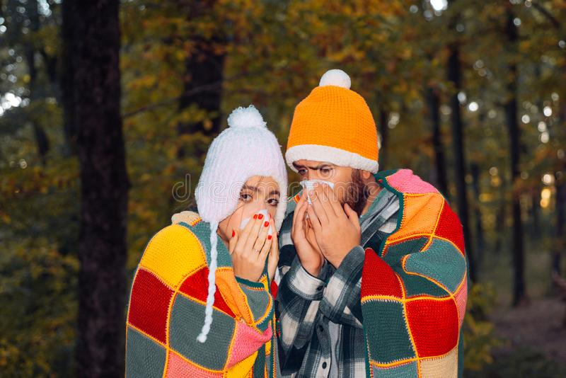 Man and woman sneezing, coughing. Sick woman and man have cold, flu and high fever. They caught a cold and now have to. Take some medicine to get better stock photography