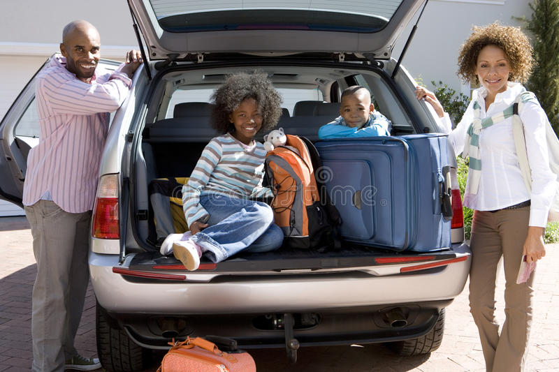 Man and woman by son and daughter (6-10) in back of car with luggage, smiling, portrait royalty free stock images