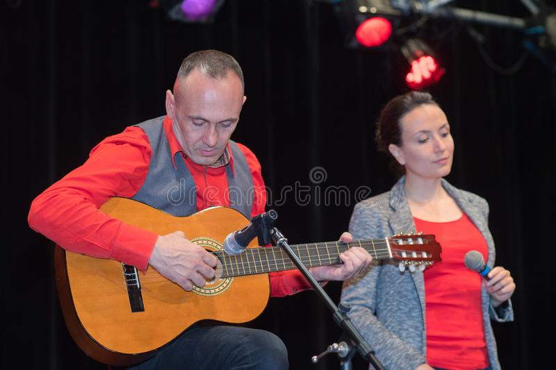 Man and woman on stage during concert. Man and women on stage during concert man royalty free stock photography
