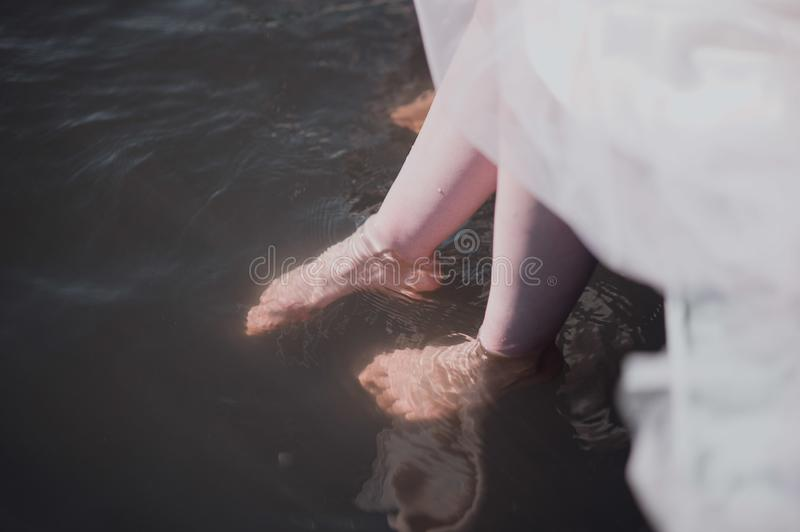 Man and woman stand with their feet in the water in the river royalty free stock photo
