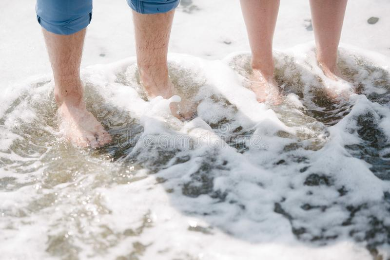 Man and woman stand with their feet in the water in the river stock photography
