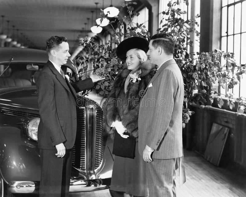 Man and woman standing in a car showroom talking to a salesman royalty free stock photo