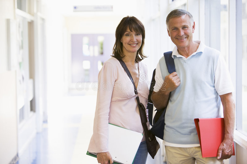 Download A Man And Woman Standing In A Corridor Stock Image - Image of binder, aged: 6080605