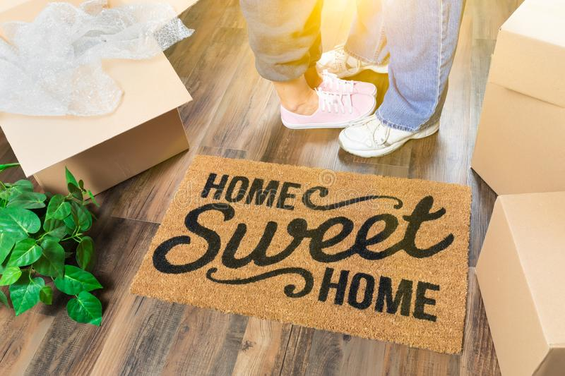 Man and Woman Standing By Home Sweet Home Welcome Mat, Moving Boxes. Man and Woman Standing Near Home Sweet Home Welcome Mat, Moving Boxes and Plant stock image