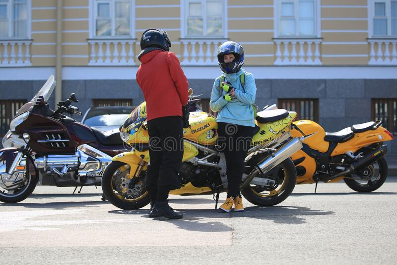 A man and a woman are standing near a custom sports bike Suzuki. Palace Square royalty free stock image