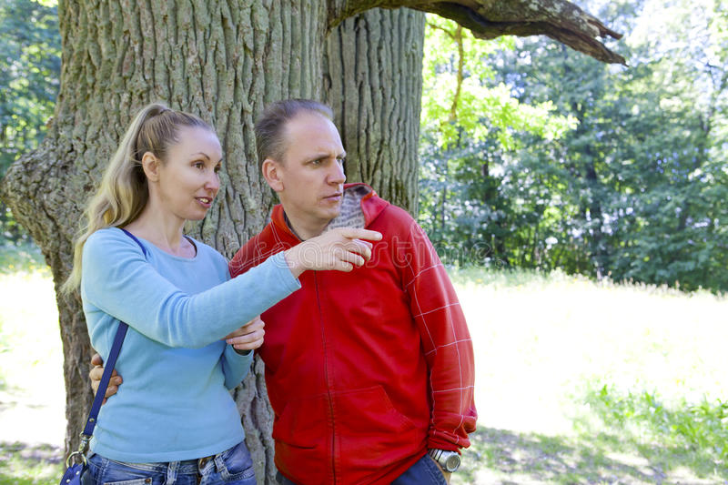 The man and the woman standing at a trunk of a huge tree, an oak show aside. The men and the women standing at a trunk of a huge tree, an oak show aside stock photo
