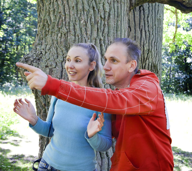 The man and the woman standing at a trunk of a huge tree, an oak show aside. The men and the women standing at a trunk of a huge tree, an oak show aside royalty free stock image