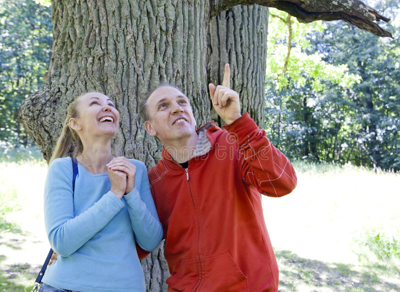 The man and the woman standing at a trunk of a huge tree, an oak show aside. The men and the women standing at a trunk of a huge tree, an oak show aside royalty free stock photos