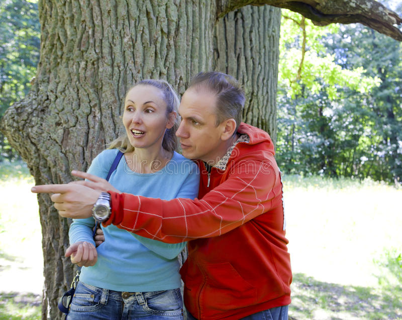 The man and the woman standing at a trunk of a huge tree, an oak show aside. The men and the women standing at a trunk of a huge tree, an oak show aside royalty free stock images