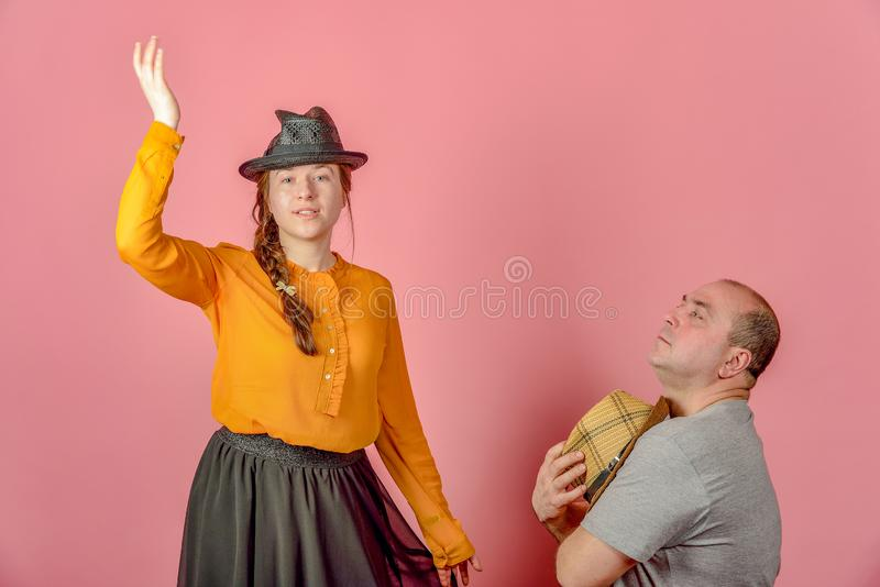A man and a woman in a straw hat on a red background posing for the camera in the studio stock photo