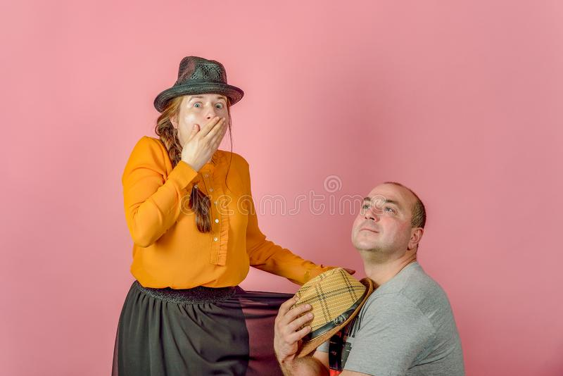 A man and a woman in a straw hat on a red background posing for the camera in the studio stock images