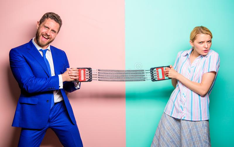Man and woman stretching expander opposite sides. Business competition between businessman and female. Gender stock photography