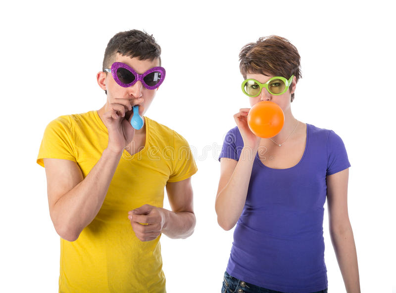 Man and woman with sunglasses blowing balloons stock images