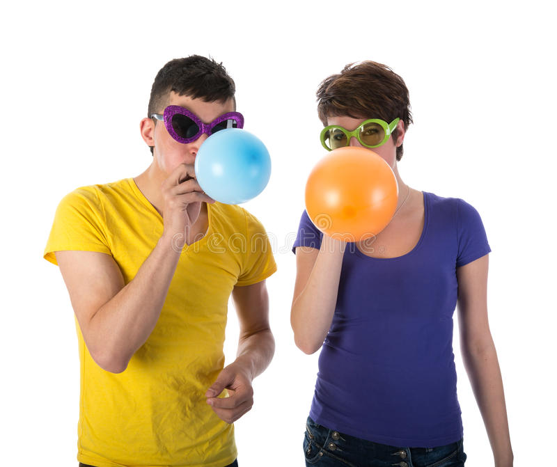 Man and woman with sunglasses blowing balloons stock image