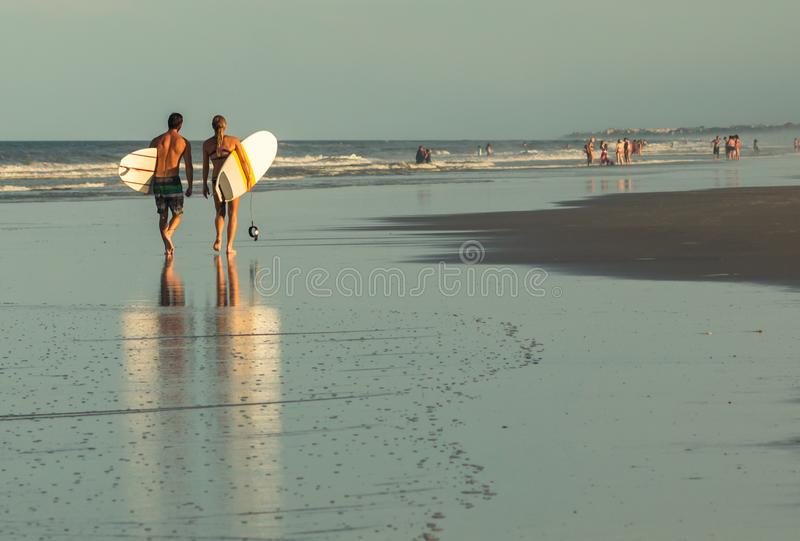 Man and Woman with Surfboards Walking on Beach at Sunset stock images