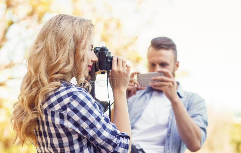 Man and woman taking photos with a camera and a smartphone in autumn park. stock photography