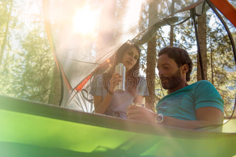 Man and woman talking in hanging tent camping in forest woods during sunny day.Group of friends people summer adventure. Man and women talking in hanging tent stock photos