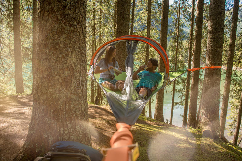 Man and woman talking in hanging tent camping in lake forest woods during sunny day.Group of friends people summer. Man and women talking in hanging tent camping royalty free stock photography