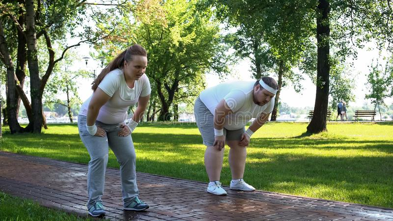 Man and woman tired after jogging in park, fitness weight loss program, cardio stock photography