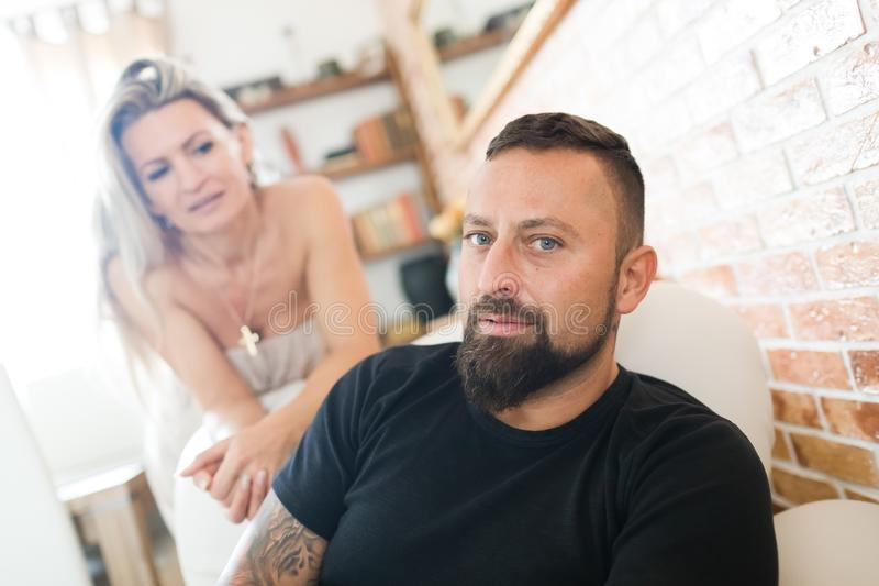 Man and woman together. Man sitting on sofa, woman standing behind royalty free stock image