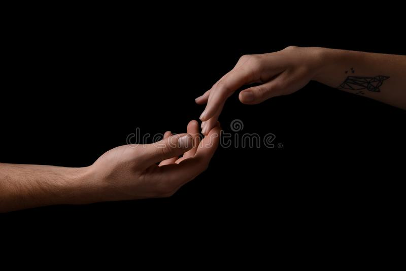 Man and woman touching fingers on dark background stock photography