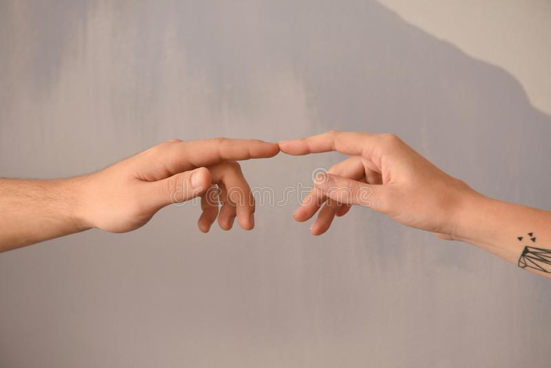 Man and woman touching fingers on grey background royalty free stock photo