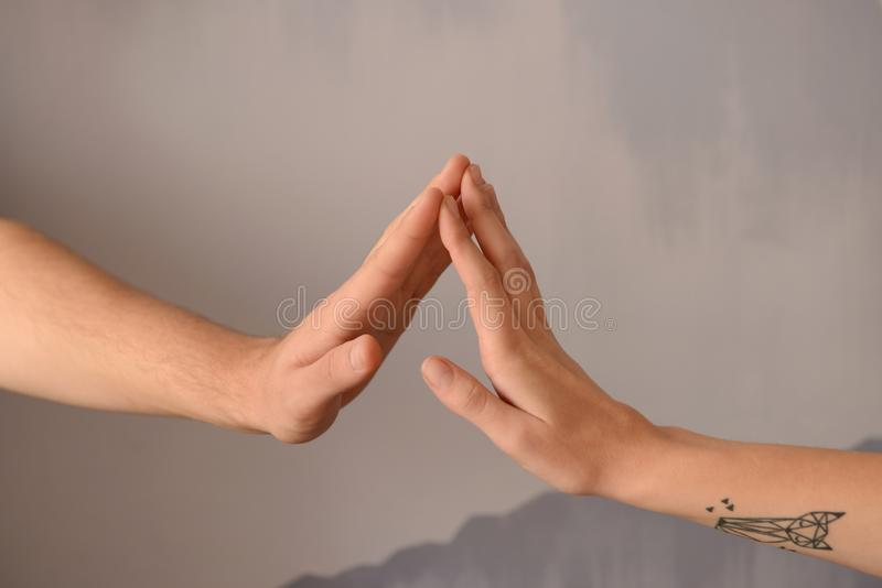 Man and woman touching fingers on grey background royalty free stock images