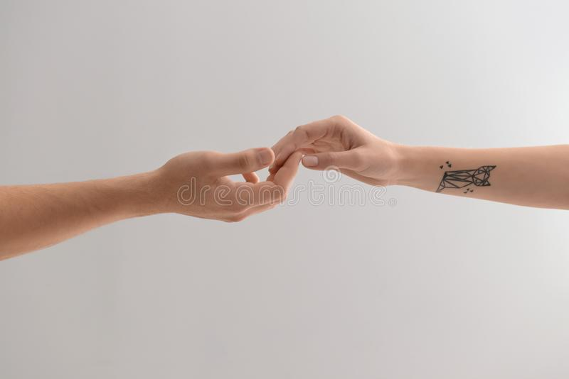 Man and woman touching fingers on light background royalty free stock photo