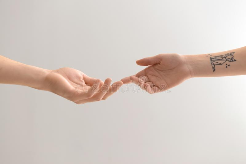 Man and woman touching fingers on light background royalty free stock images