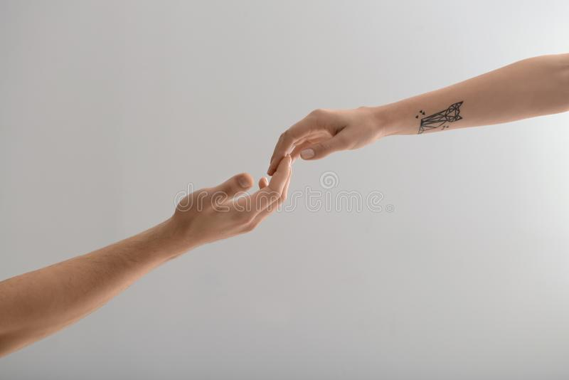 Man and woman touching fingers on light background royalty free stock image